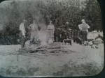 Photograph of a group of men and a woman standing around a camp fire in camp in British Columbia, Canada in the early 20th century. One of the men may be Professor Robert Wallace, another man may be Alex Easton and the woman may be Isabel Easton.